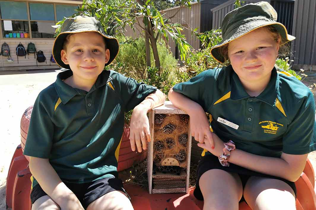 Two Red Cliffs Primary students show off their completed insect hotels